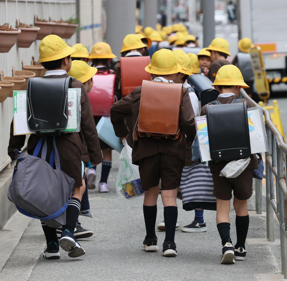 写真・図版 : たくさんの荷物を背負って下校する小学生=2020年2月28日、大阪市西区
