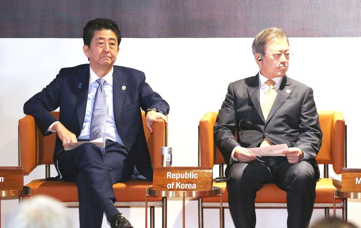 写真・図版 : ポートモレスビーで開かれたAPECビジネス諮問委員会に臨む安倍晋三首相(左)と韓国の文在寅大統領=2018年11月17日