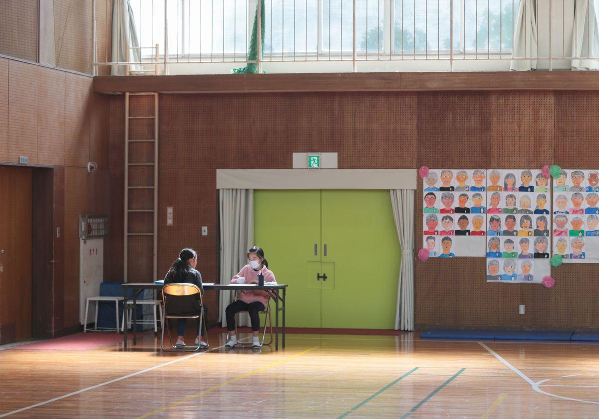 写真・図版 : 開放された体育館の片隅で自習する児童ら=2020年3月2日、愛知県豊明市の市立栄小学