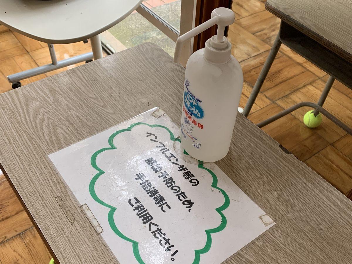 写真・図版 : 学校の来客用玄関に置かれた消毒液=岩崎撮影