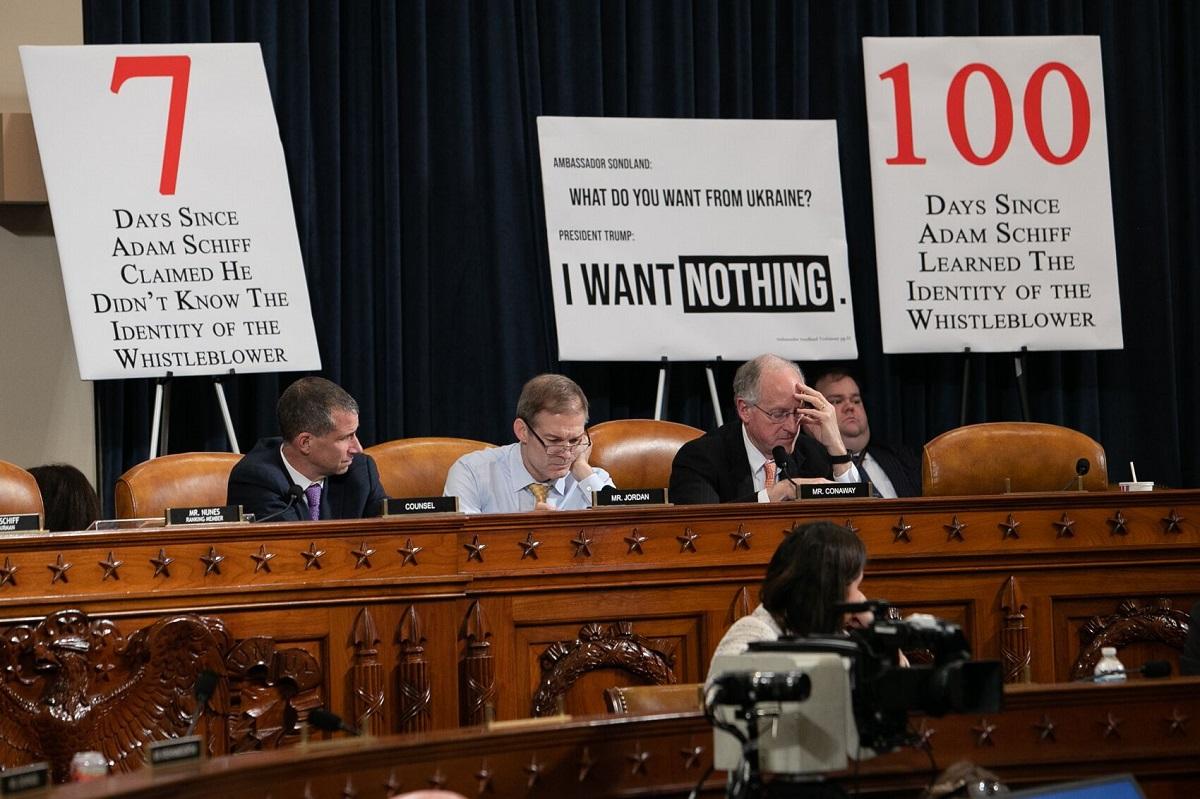写真・図版 : トランプ大統領の弾劾調査を進める米下院の公聴会に出席する共和党議員ら。背後には、トランプ大統領の言動を擁護したり、下院情報委員会のシフ委員長を批判するプラカードが並べられた=ワシントン、ランハム裕子撮影、2019年11月20日