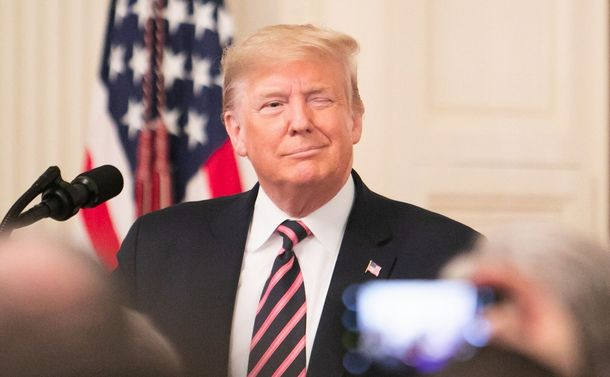 写真・図版 : 弾劾裁判で無罪となった翌日、共和党議員らの大きな拍手と歓声を浴びながらホワイトハウスのイーストルームに登場し、ウィンクするトランプ大統領=ワシントン、ランハム裕子撮影、2020年2月6日