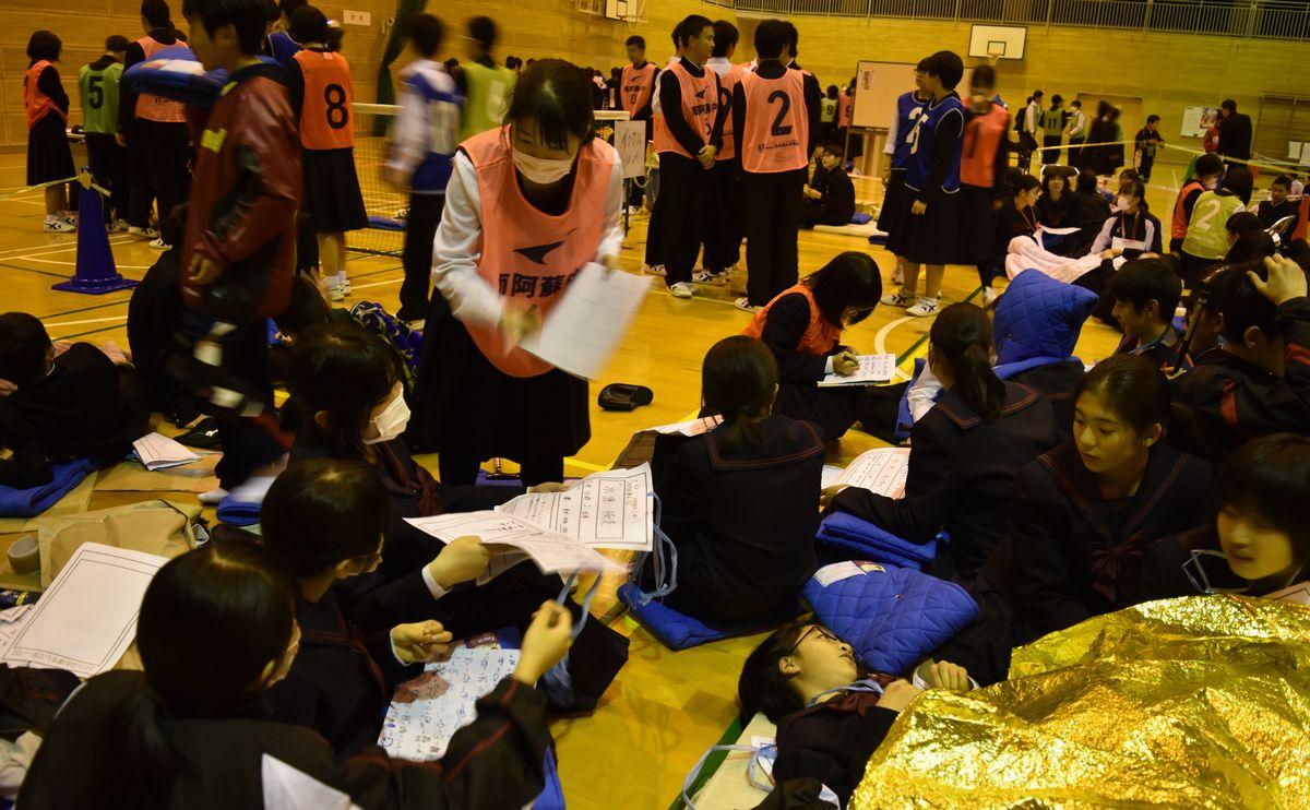 写真・図版 : 避難所運営の訓練で、避難者の居住地や状況を確認し名簿を作った参加者=2019年12月19日、熊本県南阿蘇村河陽の南阿蘇中