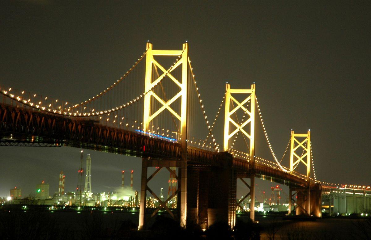 写真・図版 : 与島パーキングエリアから見た瀬戸大橋。背後は坂出市沿岸の工場街=同市与島町で