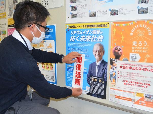 写真・図版 : 行事の中止・延期が全国で相次いでいる。静岡県富士市庁舎で掲示板の講演会ポスターに延期のラベルを貼る市職員。右のポスターのランニングイベントは中止になった=2020年2月20日、富士市永田町、六分一真史撮影