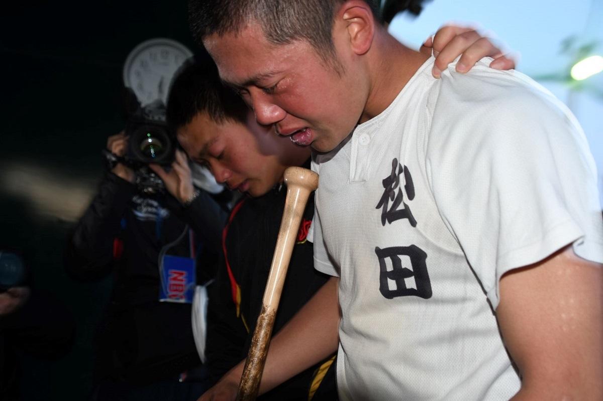春の選抜大会の中止が決まり、泣きながら道具を片付ける長崎・創成館の選手たち=2020年3月11日