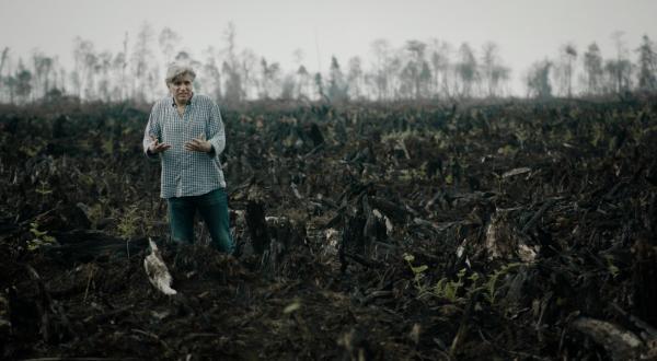 インドネシア、スマトラ島。アブラヤシ農園拡大のために焼かれた熱帯雨林に立つ『グリーン・ライ ~エコの嘘~』のブーテ監督©e&a film