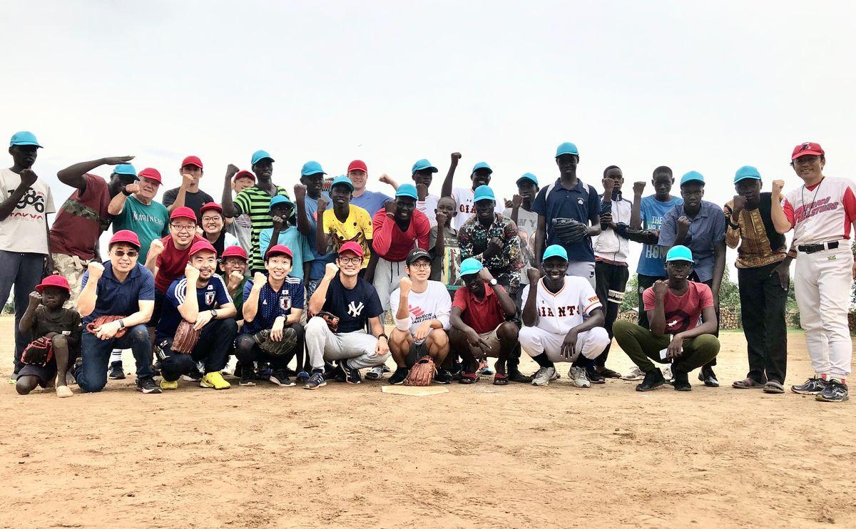 写真・図版 : 南スーダン野球団とオールジャパンチームの合同記念撮影。オールジャパンチームには、アメリカ人、韓国人なども加わり多国籍軍となって勝利した。