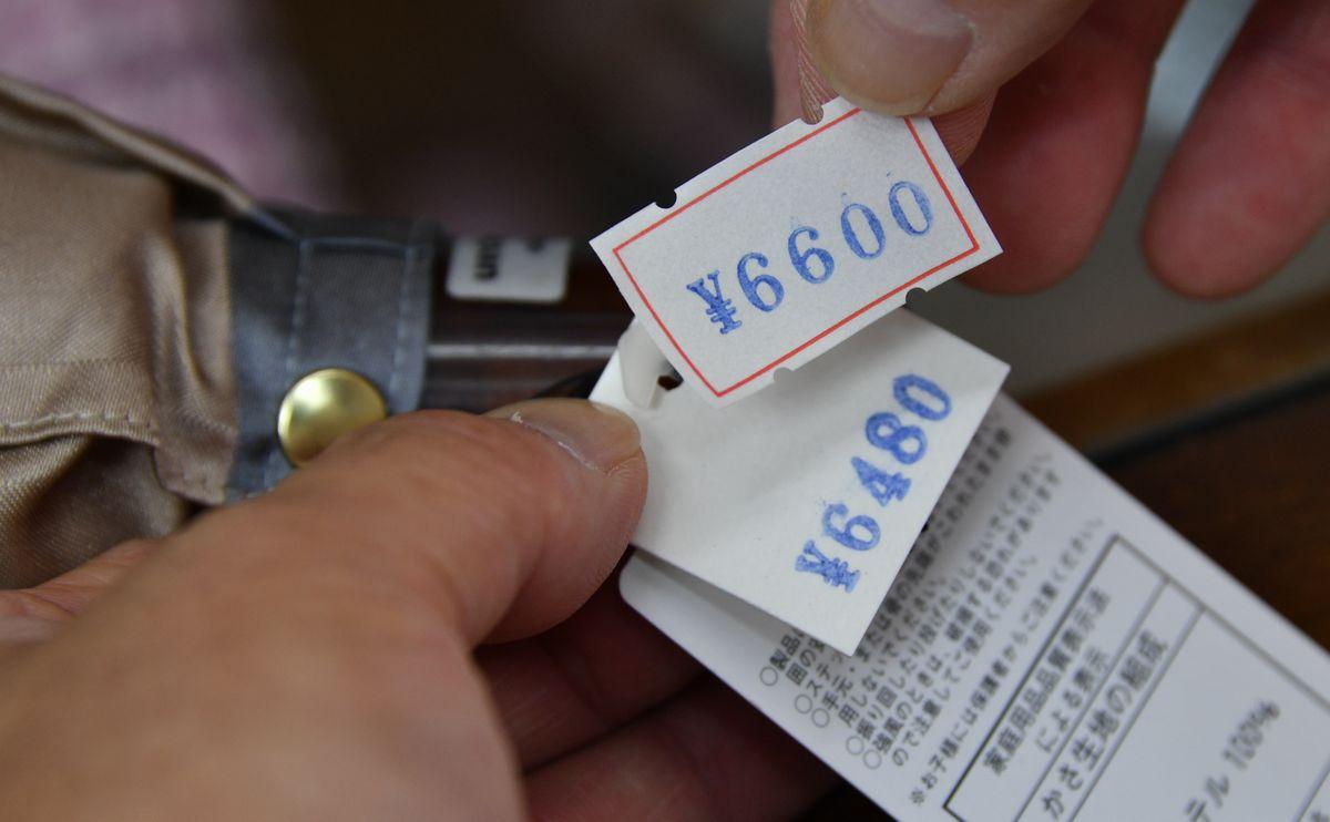 写真・図版 : 消費税増税初日、都内の洋傘店内では消費税8%から10%の値札への張り替え作業が行われた=2019年10月1日、東京都豊島区