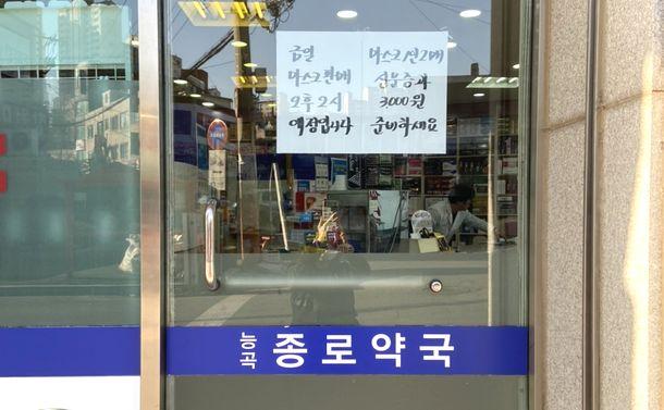 写真・図版 : 薬局ごとに何時から販売すると書いてある。この薬局は午後2時から。一人二枚、3000ウォン=筆者撮影