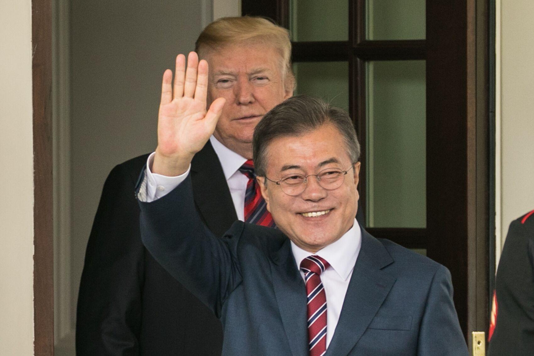 写真・図版 : ホワイトハウスでトランプ大統領(奥)に迎えられ、記者団に手を振る韓国の文在寅大統領=ワシントン、ランハム裕子撮影、2018年5月22日