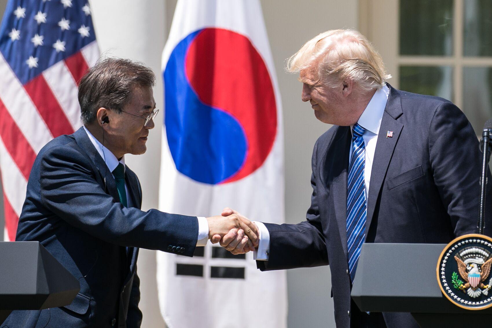 写真・図版 : ホワイトハウスで行われた共同記者会見で握手する韓国の文在寅大統領(左)とトランプ大統領=ワシントン、ランハム裕子撮影、2017年6月30日