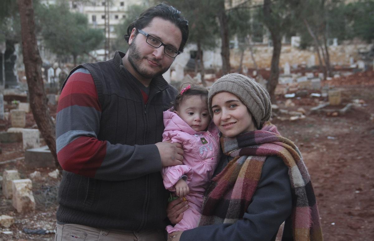 写真・図版 : 右から、『娘は戦場で生まれた』のワアド・アルカティーブ監督、娘のサマちゃん、夫で医師のハムザさん。2016年12月、反体制派が拠点としたシリア北部アレッポで撮影した家族写真=本人提供