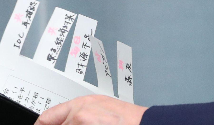 写真・図版 : 記者会見に臨む菅義偉官房長官が持つ書類には「森友」などの印がついていた=2020年3月18日