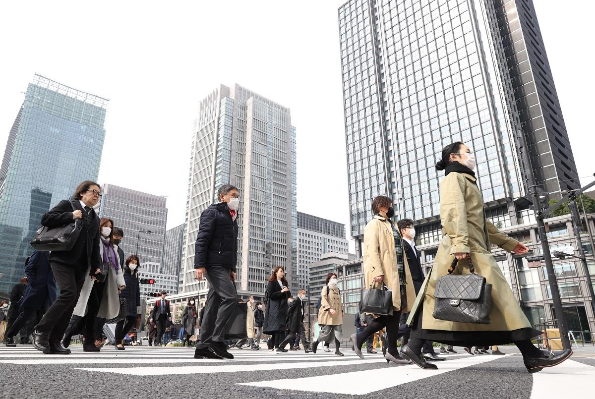 写真・図版 : 東京・丸の内 でマスクを着用して出勤する人たち=2020年3月30日