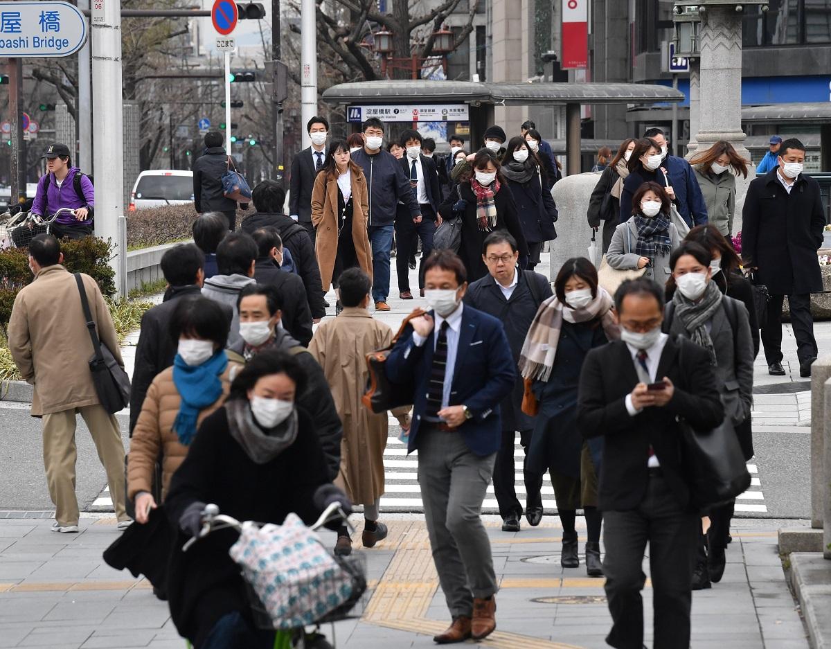 写真・図版 : 週末の外出自粛要請から一夜明け、普段通り通勤する人たち=2020年3月30日、大阪市北区