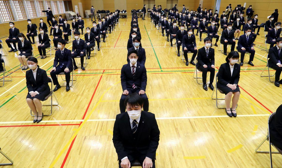 写真・図版 : 大阪メトロの入社式に参加する新入社員たち。通常より間隔を広めに空けて式に臨んだ=2020年4月1日午前10時25分、大阪市西区