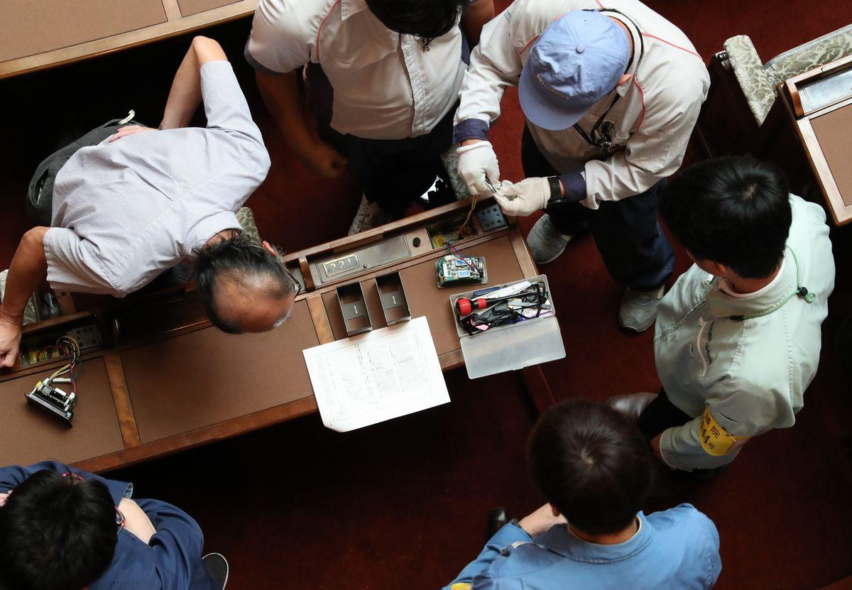 臨時国会開会を前に、れいわ新選組の木村英子さん、舩後靖彦さんの議席に押しボタンを移設する工事が進められた=2019年9月20日午前10時19分