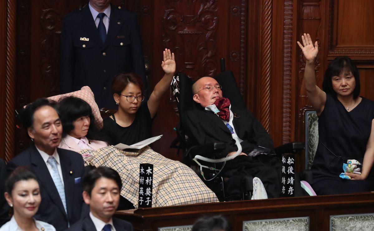 写真・図版 : 臨時国会の会期を決める採決で、起立する代わりに介助者が手を挙げて賛成する木村英子さん(左)と舩後靖彦さん=2019年8月1日午後1時1分