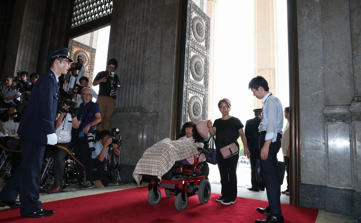 写真・図版 : 介助者とともに初登院する「れいわ新選組」の木村英子さん(中央)=2019年8月1日午前9時30分