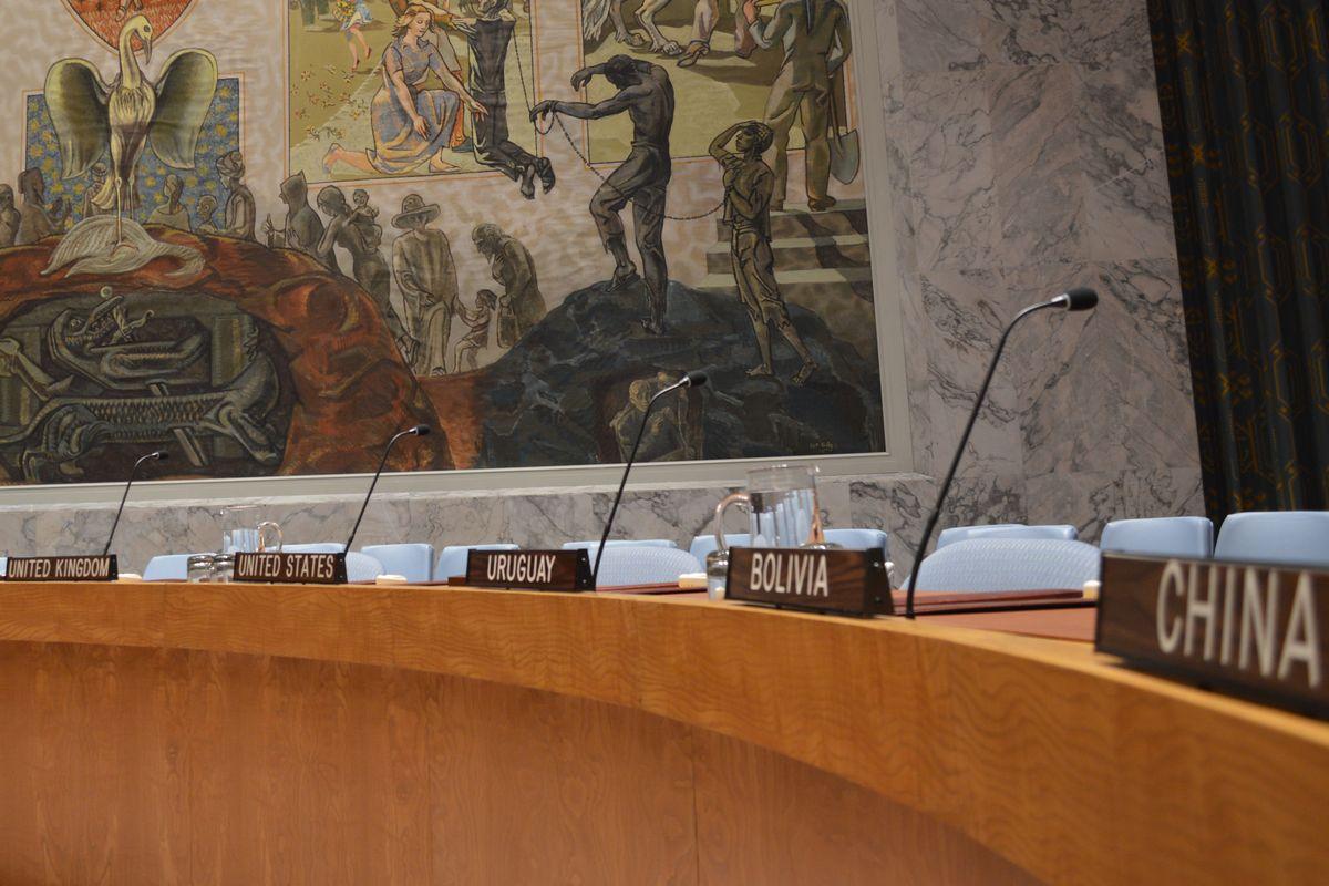 写真・図版 : 国連安保理の公式協議の議場。15理事国の席が国名のアルファベット順に並ぶ。手前の中国と、奥から英国、米国はいずれも常任理事国。
