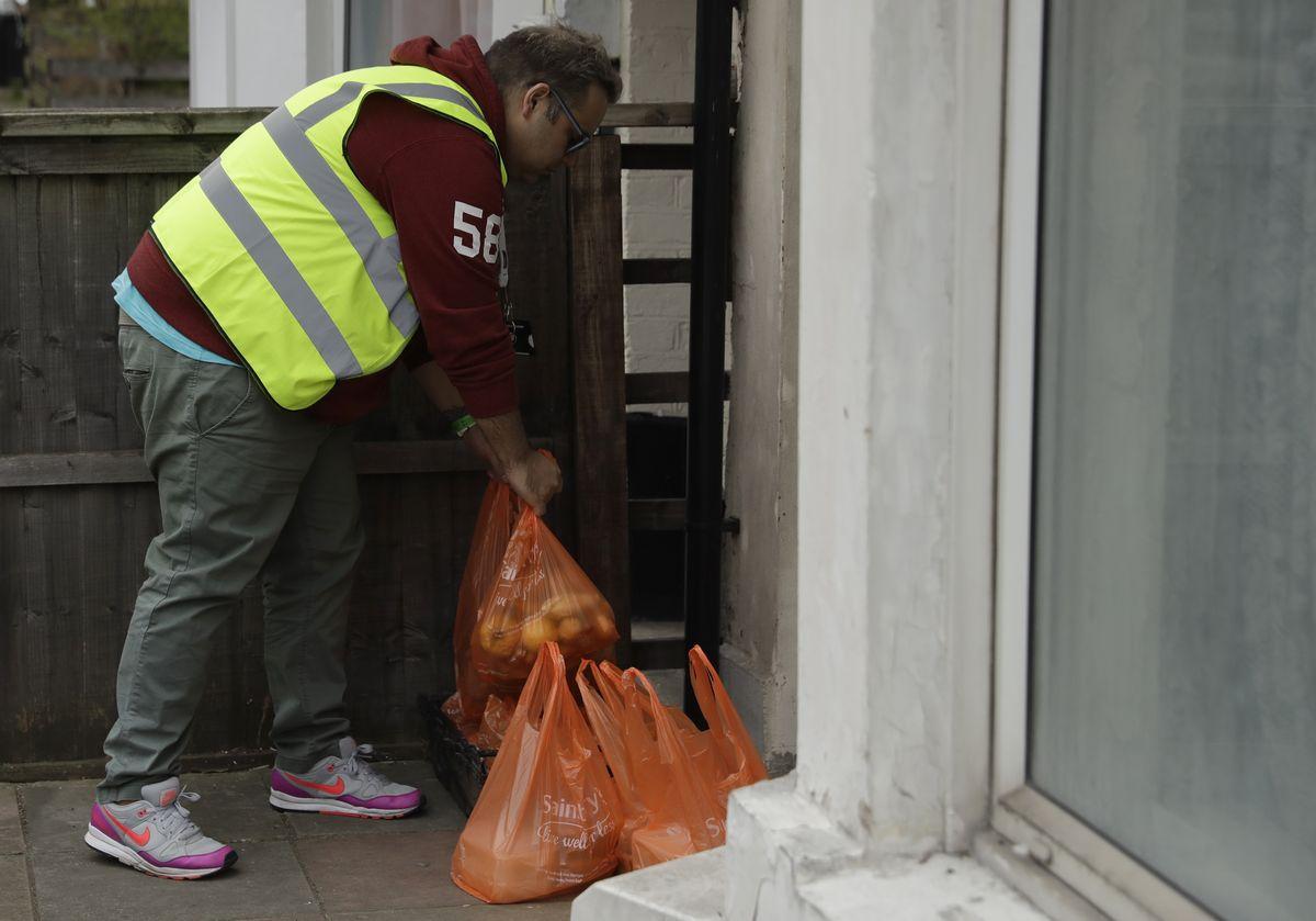 写真・図版 : イギリスのロンドン北部では、慈善団体が寄付された食料や生活必需品が生活弱者に届けられている=2020年4月1日、AP