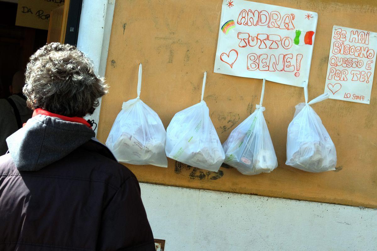 写真・図版 : イタリアのローマでは、生活に困った人たちのために、商店の人たちが食料品などを袋に詰め、自由に持ち帰れるように提供している=2020年4月3日、AP