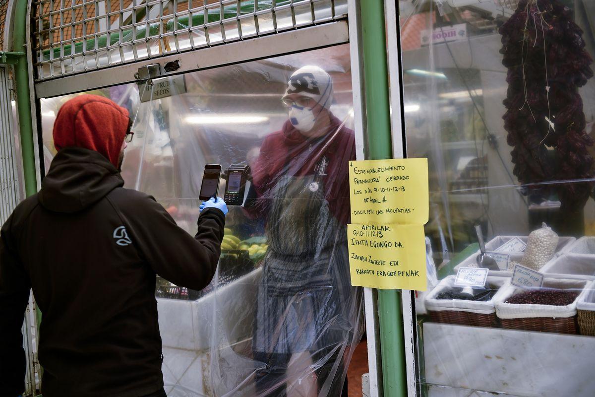 写真・図版 : 2020年4月2日、スペイン北部のパンプローナでは、市場の露店が新型コロナウイルスの感染拡大を防ぐため、ビニールで周囲と露店遮り、お客とは携帯電話でやりとりして支払いをしている=AP