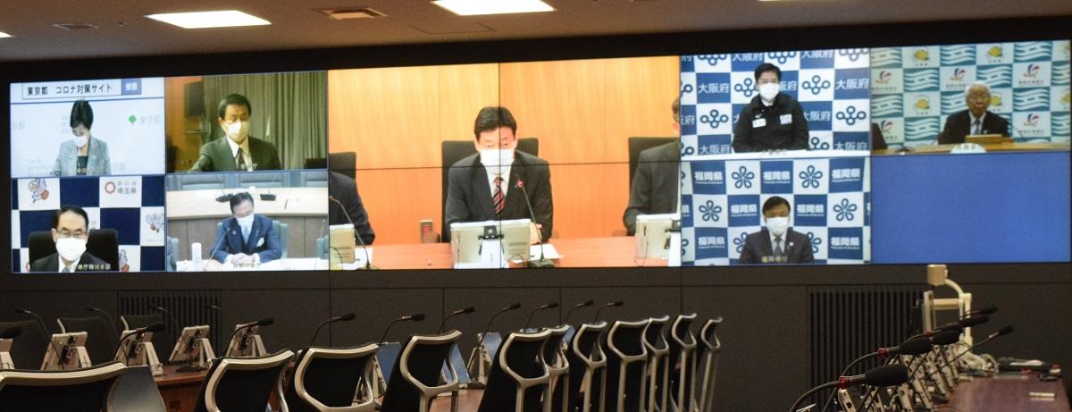 写真・図版 : テレビ会議に臨む西村康稔経済再生相(画面中央)と7都府県知事=2020年4月8日、内閣府