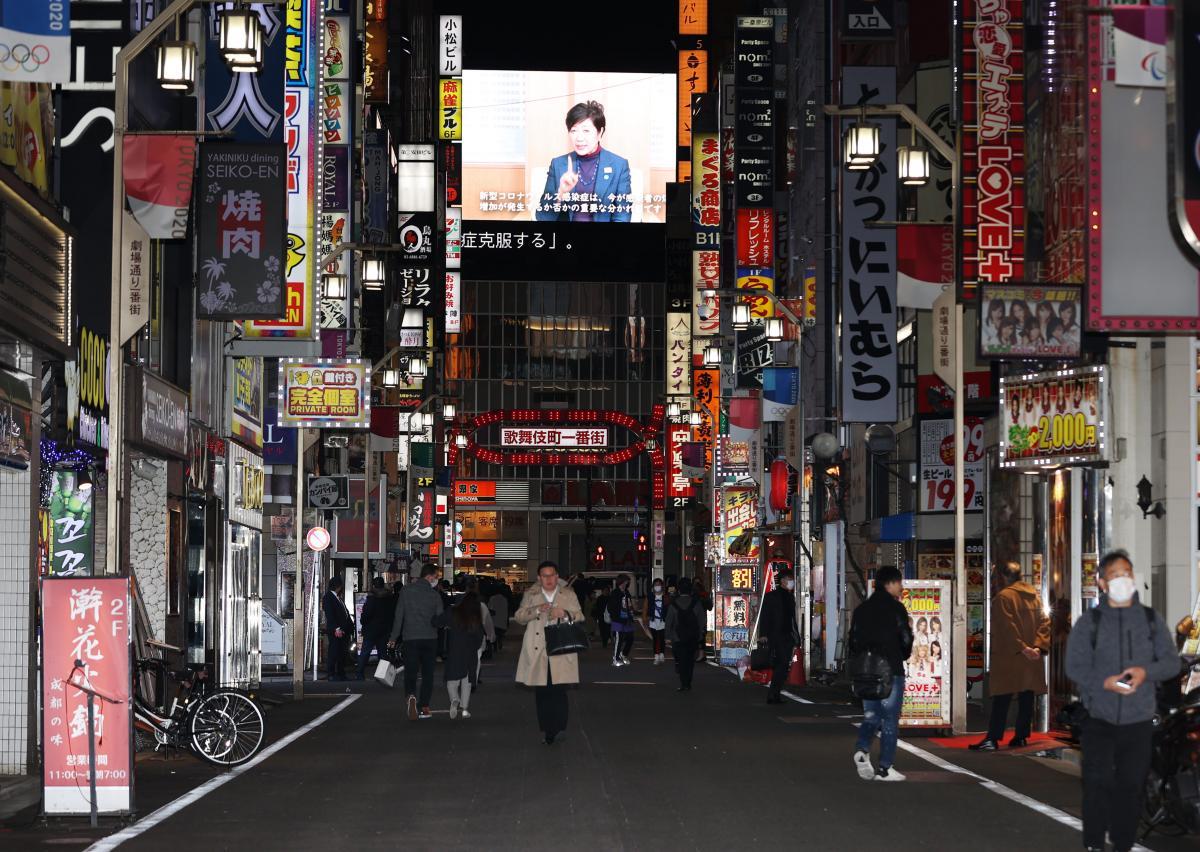 写真・図版 : 人影がまばらな新宿・歌舞伎町の繁華街。奥の大型ビジョンには、外出自粛などを呼びかける東京都の小池百合子知事が映し出されていた=2020年4月10日、東京都新宿区