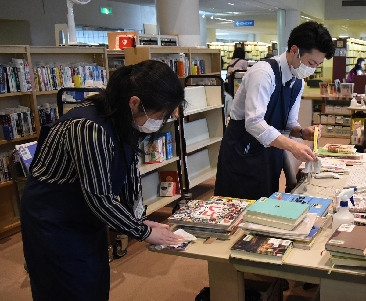 写真・図版 : 返却された本を消毒する図書館職員=2020年3月28日、秋田市