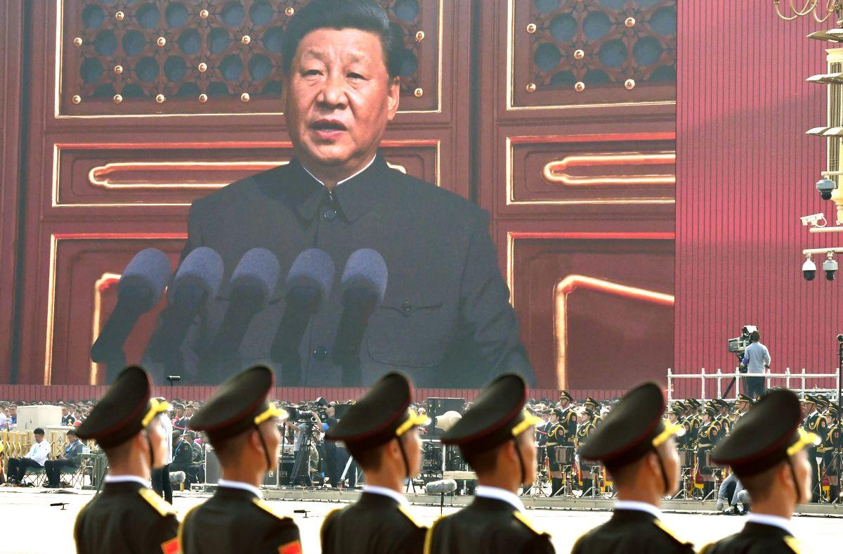 写真・図版 : 中国建国70周年の記念式典の冒頭、あいさつする習近平国家主席の姿が大画面に映し出された=2019年10月1日、北京