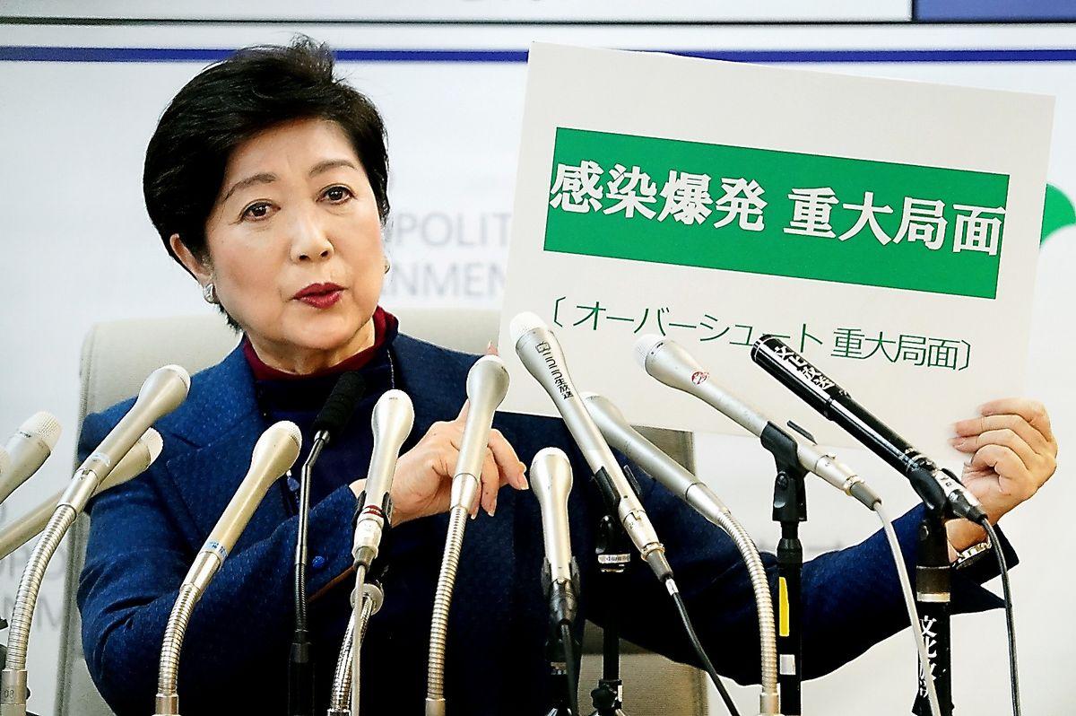 写真・図版 : 緊急記者会見で「感染爆発 重大局面」と示す東京都の小池百合子知事。「オーバーシュート」の文字も見える=2020年3月25日午後8時17分、東京都庁