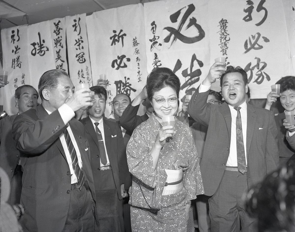 写真・図版 : 参院選当確の発表にジュースで乾杯する、藤原あき氏=1962年7月2日