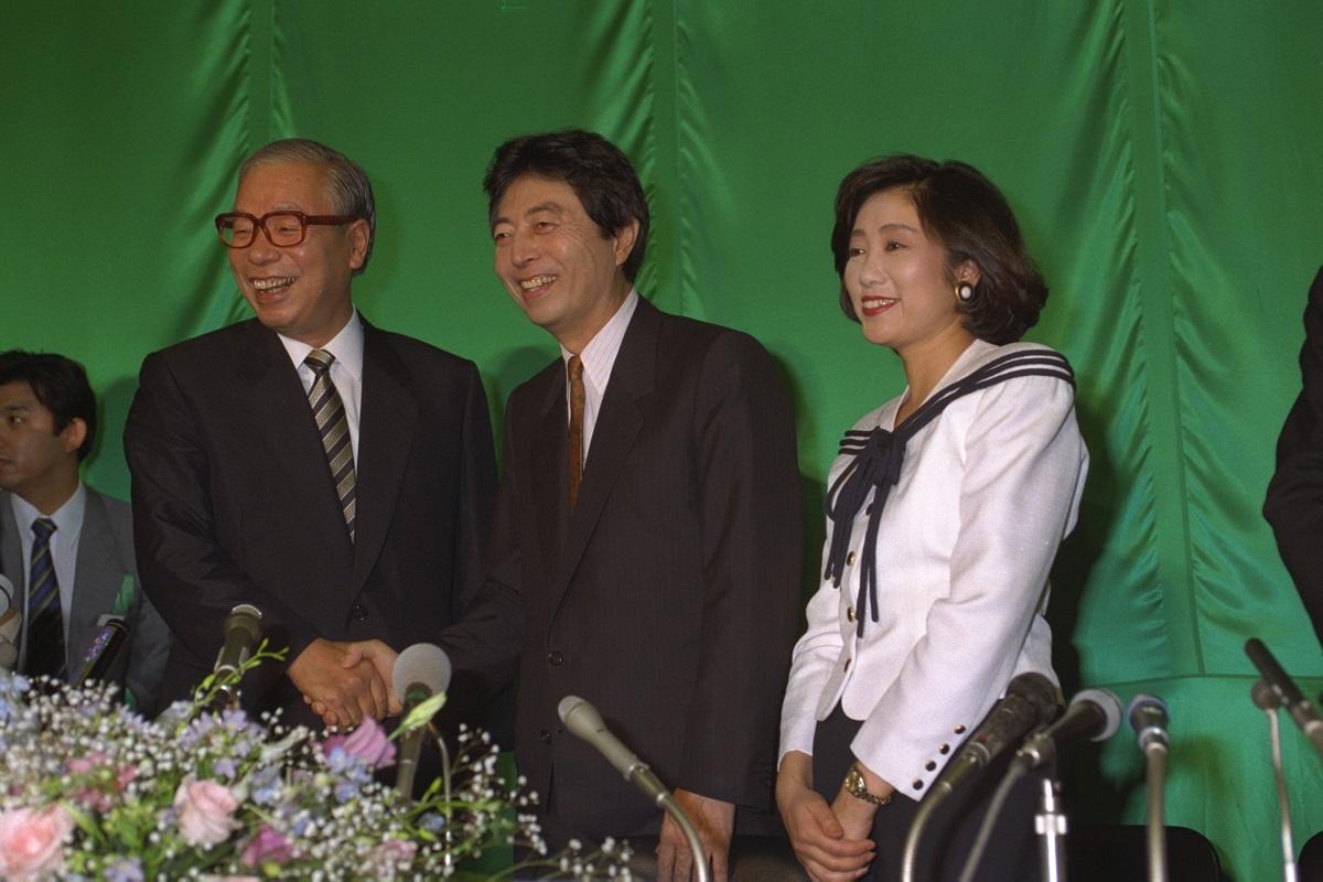 写真・図版 : 東京都議会議員選挙での大量当選に喜ぶ日本新党の細川護煕代表(中央)と小池百合子・選対本部長(右)。左は新党さきがけの武村正義代表=1993年6月27日  、 東京都港区
