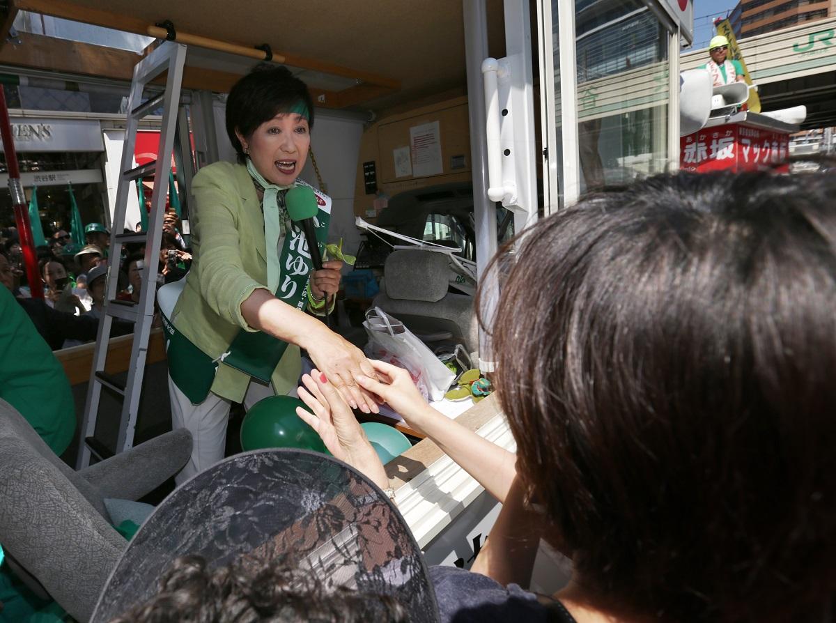 写真・図版 : 都知事選に立候補、有権者と握手する小池氏=2016年7月29日、東京都渋谷区