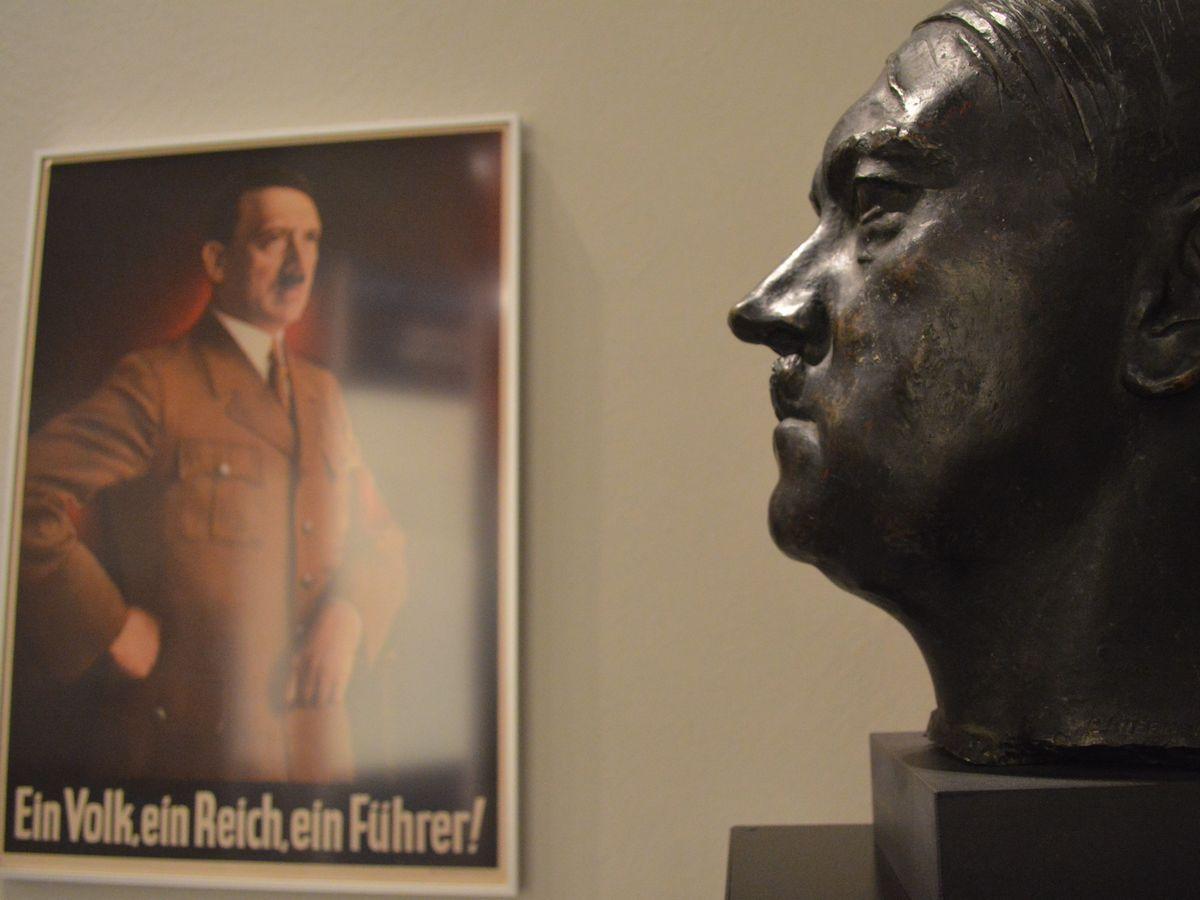 写真・図版 : ヒトラーの顔の像と、「一つの民族、一つの帝国、一人の指導者!」を訴えるナチスのポスター=2月、ベルリンの国立ドイツ博物館。藤田撮影