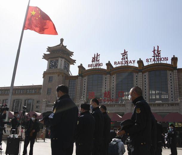 写真・図版 : 北京駅前で半旗を前に新型コロナウイルスの犠牲者に黙禱を捧げる治安維持の職員ら=2020年4月4日、平井良和撮影