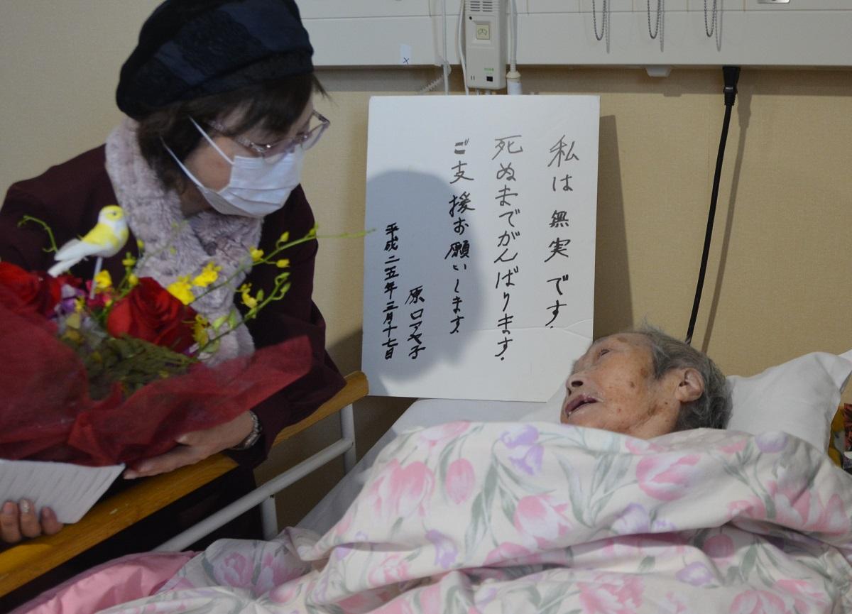 写真・図版 : 弁護団事務局長の鴨志田祐美弁護士から花を贈られる原口アヤ子さん=2020年1月16日