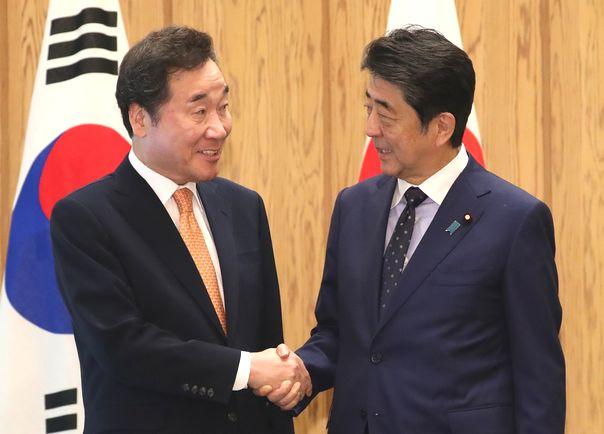 写真・図版 : 韓国の李洛淵首相(左)との会談冒頭、握手を交わす安倍晋三首相=2019年10月24日、首相官邸
