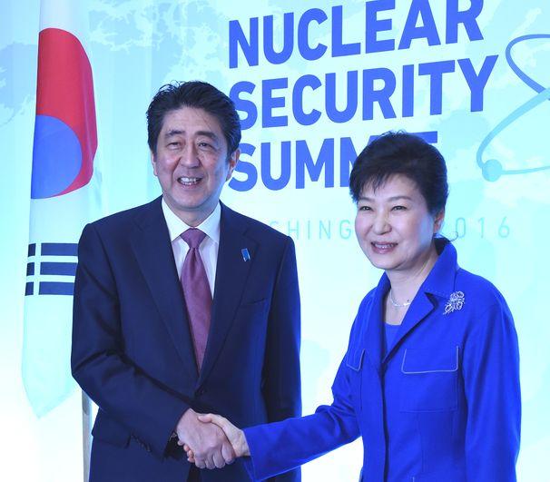写真・図版 : 首脳会談前に握手する韓国の朴槿恵大統領(右)と安倍晋三首相=2016年3月31日、ワシントン、内閣広報室提供
