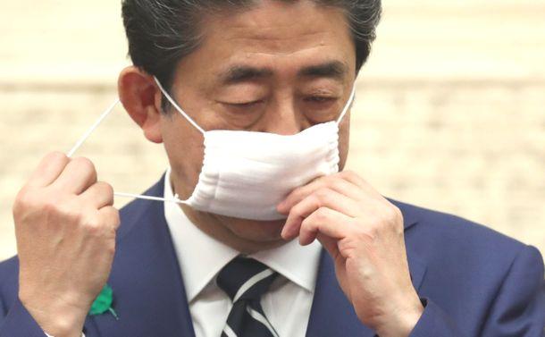 写真・図版 : 記者会見の冒頭、マスクを外す安倍晋三首相=2020年4月17日、首相官邸