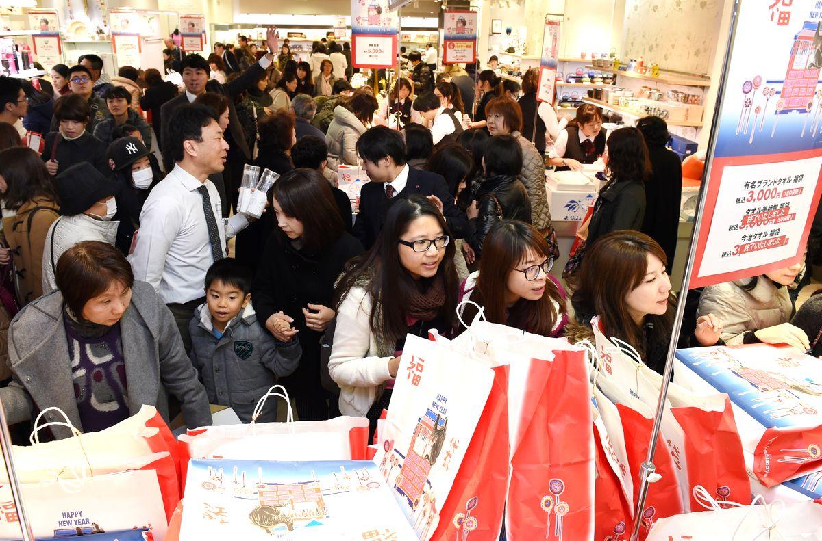 写真・図版 : 初売りで福袋を買い求める人たち。外国人観光客の姿も多かった=2016年1月2日、大阪市中央区の高島屋大阪店