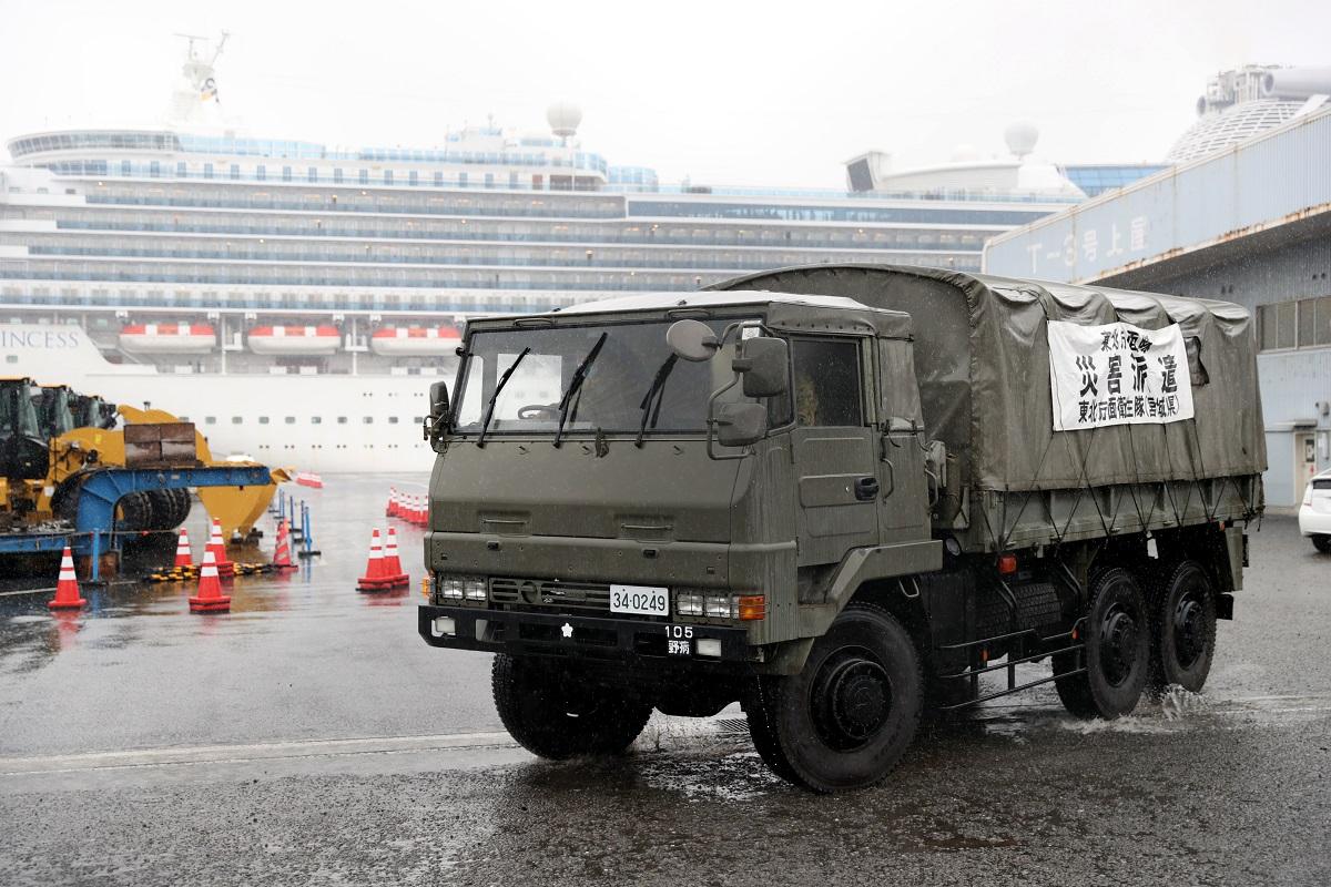 写真・図版 : ダイヤモンド・プリンセス号(奥)が停泊する大黒ふ頭から出る自衛隊の車両=2020年2月16日、横浜市