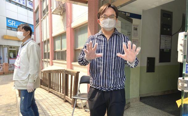 写真・図版 : 総選挙の投票所ではマスク着用が義務。使い捨て手袋を配布され、間隔を置いて並んだ