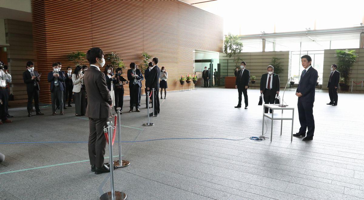 写真・図版 : 緊急事態宣言についての取材にこたえる安倍晋三首相(右)。記者との間が広い=2020年4月21日午前、首相官邸