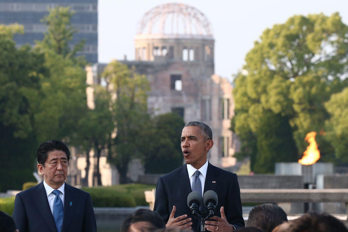 写真・図版 : 原爆死没者慰霊碑への献花を終え、所感を語るオバマ米大統領と、安倍首相=16年5月、広島市中区の平和記念公園。代表撮影