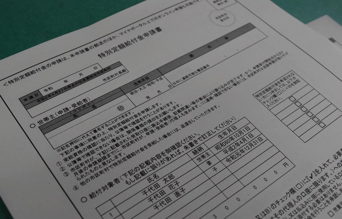 総務省が公表した郵送の場合の申請書の様式案。世帯主が受給者として氏名や住所を書き込むほか、給付金の振込先として原則、世帯主名義の金融機関の口座情報を記載するよう求めている.