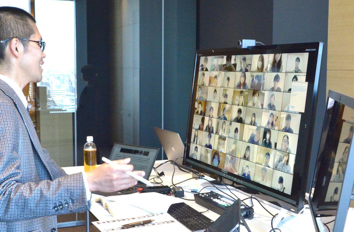 写真・図版 : 名古屋商科大による遠隔講義。パソコンの画面に学生の顔が並び、それぞれ発言していた=2020年4月7日、名古屋市中区
