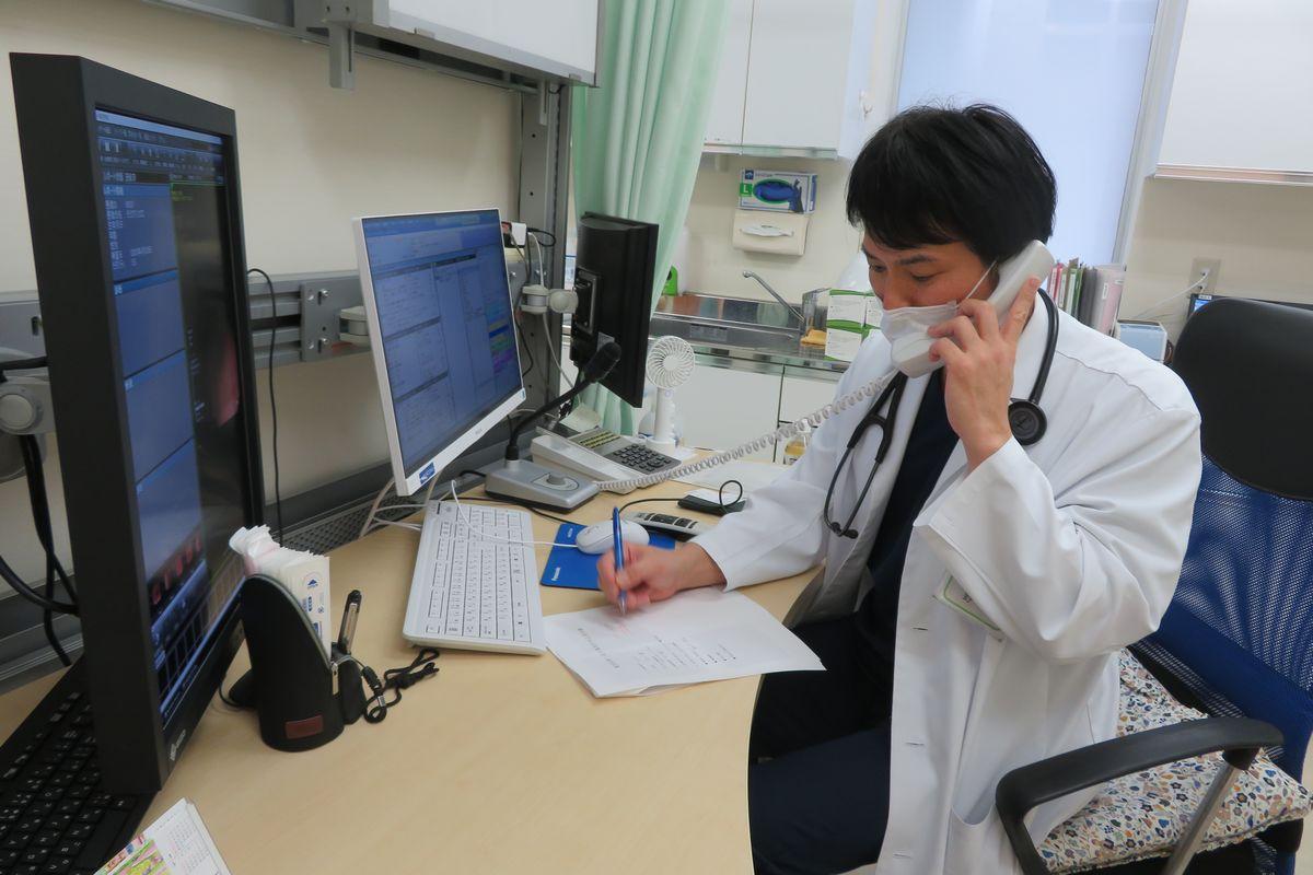 写真・図版 : 電話で診察する「のなか医院」の野中雄也院長(筆者撮影)